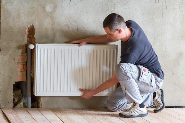 新しく建てられたアパートや家の空の部屋に暖房ラジエーターをインストールする若いハンサムなプロ配管工。建設、メンテナンス、修理のコンセプト。