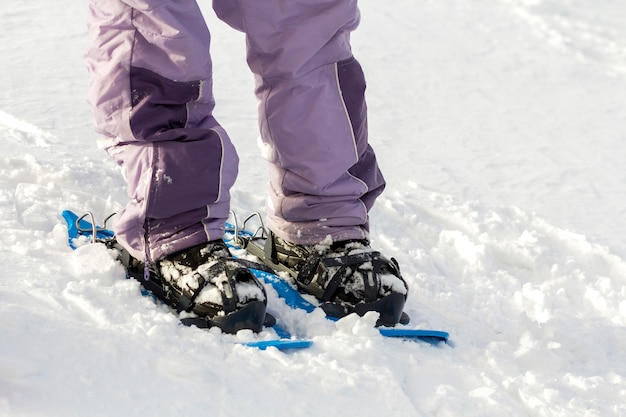 Конец-вверх ног и лыжника человека вкратце пластичных ярких профессиональных широких лыж на космосе экземпляра белого снега солнечном. активный образ жизни, зимние экстремальные виды спорта и отдыха концепции.