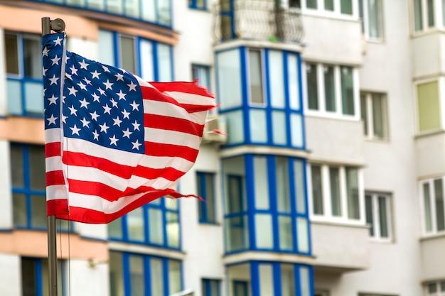 街のスカイラインに対して米国旗のクローズアップ