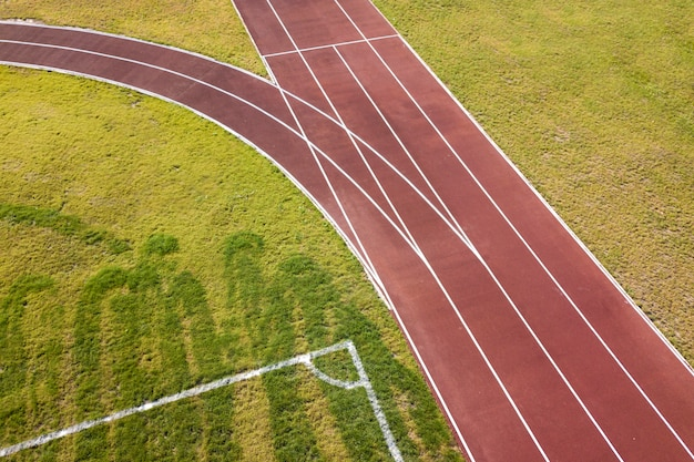 赤いランニングトラックと緑の芝生の芝生の平面図です。スポーツ活動のためのインフラ。