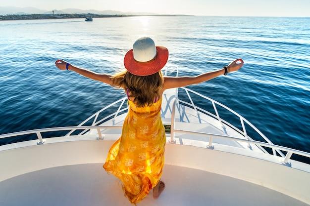 黄色いドレスと青い海の水の景色を楽しみながら白いヨットのデッキに上げられた手で立っている麦わら帽子を身に着けている長い髪の若い女性。