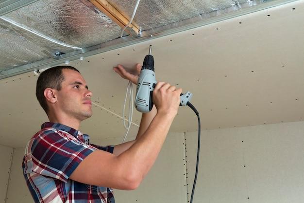 乾式壁を天井に固定する労働者。