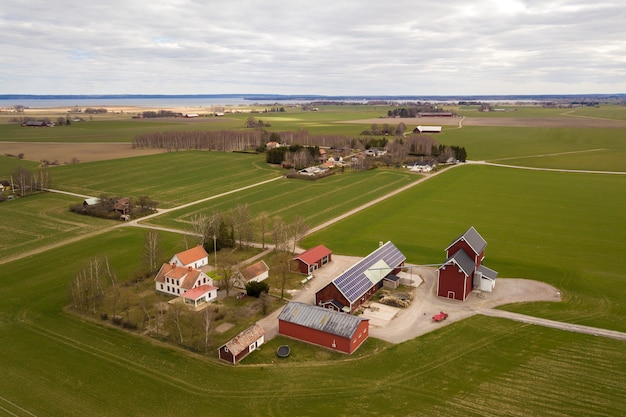 晴れた春の日の田園風景の平面図です。木造の建物、納屋、家の屋根に太陽光発電太陽光発電パネルシステムを備えた農場。