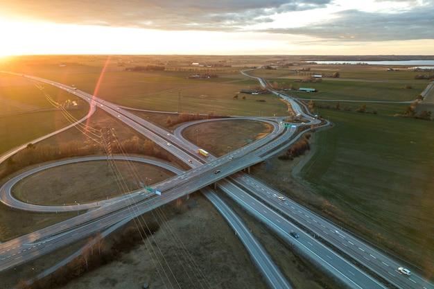 昇る太陽の夜明けに近代的な高速道路道路交差点の空撮。ドローン写真。