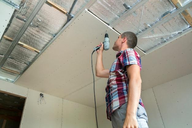 吊り天井を固定する労働者。