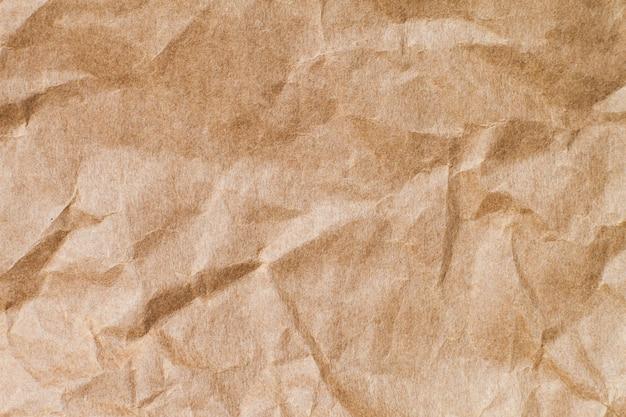 背景の抽象的な茶色のリサイクルしわくちゃの紙:デザイン、装飾用の茶色の紙の折り目。