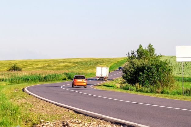 夏のアスファルト道路を移動する車