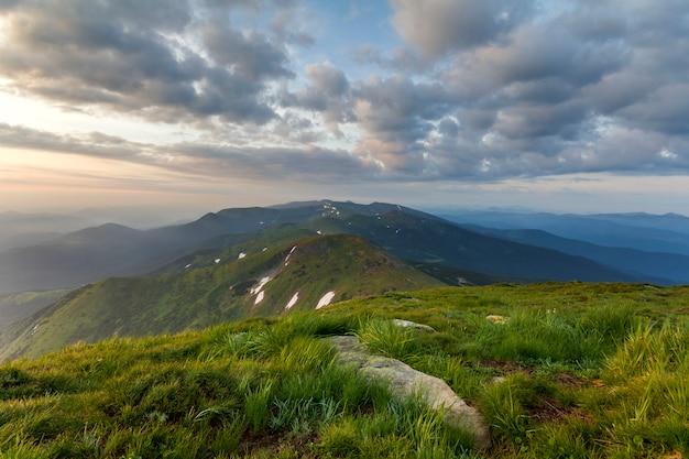 日の出の広い夏のマウンテンビュー。大きな岩と遠くの山脈が朝の霧で覆われている緑の草が茂った丘の上に青い曇り空を上げる輝くオレンジ色の太陽。自然概念の美しさ。