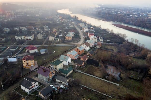 町を流れる川の空撮。春または秋の日の住宅、道路、樹木の田園風景。ドローン写真。