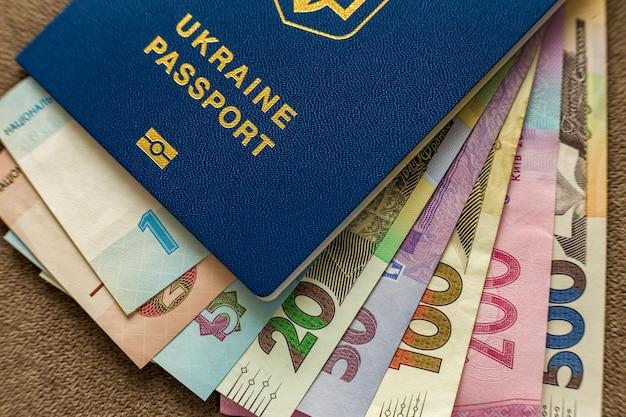 ウクライナのパスポートとお金、ウクライナグリブナ紙幣手形コピースペース、トップビュー。旅行と金融の問題の概念。