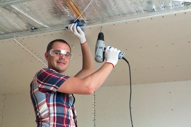 光沢のあるアルミ箔で断熱された天井に電動ドライバーを使用して乾式壁吊り天井を金属フレームに固定するゴーグルの若い男。改修、建設、自分でやるコンセプト。