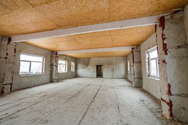 再建中の未完成のアパートまたは家の大きなロフトルーム。合板の天井、漆喰壁、窓の開口部、セメントの床。建設と改修のコンセプトです。