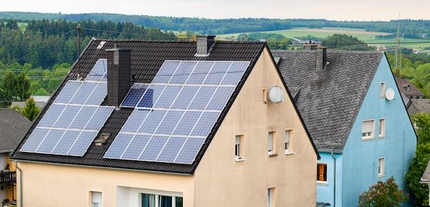 Возобновляемые экологически чистые энергосберегающие эффективные солнечные батареи на крыше загородного дома.