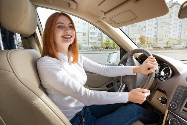 Молодая рыжая женщина водитель за рулем за рулем автомобиля, счастливо улыбаясь