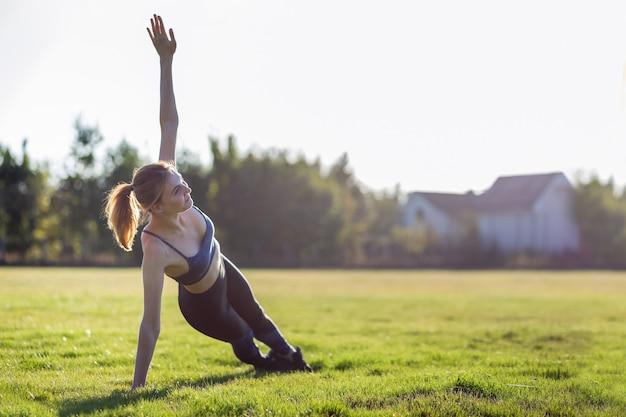 Молодая спортивная женщина в спортивной одежде, обучение в поле на рассвете