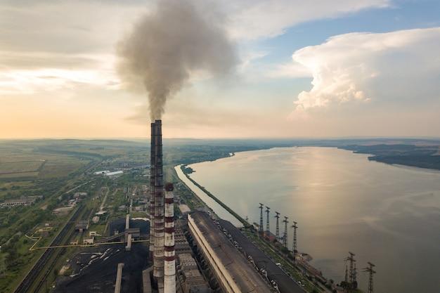 石炭発電所からの灰色の煙が付いている高い煙突の管