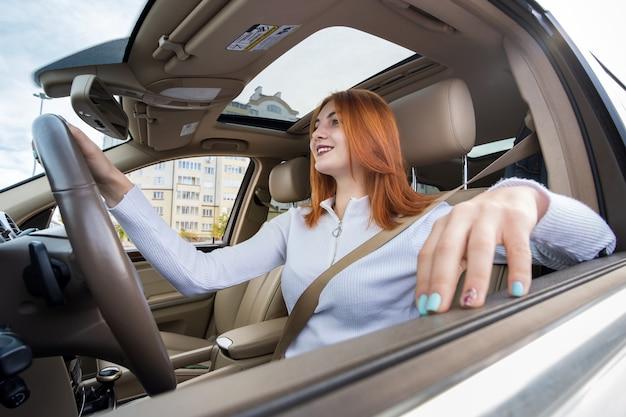 幸せそうに笑って車を運転してシートベルトで固定された若い赤毛の女性ドライバー