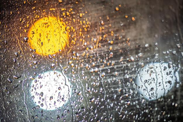 水滴とぼやけた街の明かりとガラスの表面。
