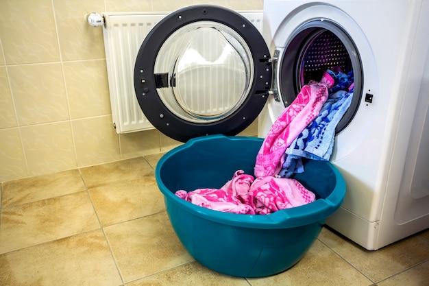 Разноцветная одежда и полотенца в барабане стиральной машины