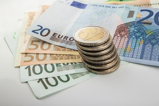お金のユーロ硬貨と紙幣は異なる位置で互いに積み重ねられます。お金の概念。机の上のユーロ通貨の詳細。
