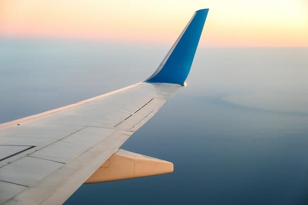晴れた朝の海の風景の上を飛んでいる航空機の白い翼の飛行機からの眺め。空の旅と輸送の概念。