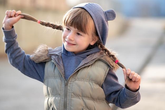Портрет счастливой девочки ребенка с косами волос в теплой одежде осенью на открытом воздухе.