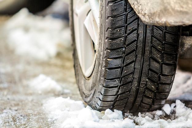 雪に覆われた道路の冬タイヤで車のホイールのクローズアップ