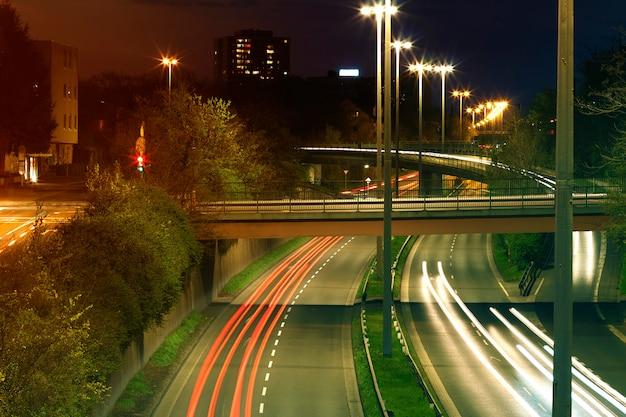 道路に焦点を当てた都会の夜間交通のある高速道路。高速道路上の車の道