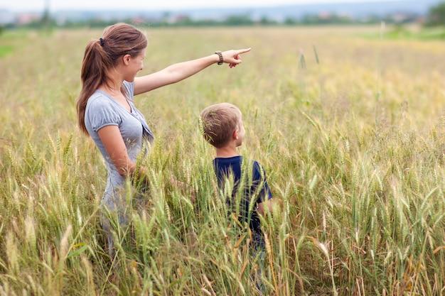 手と小さな男の子を指している若い女性彼女の息子は麦畑に立っています。自然と道の概念を示す統一。