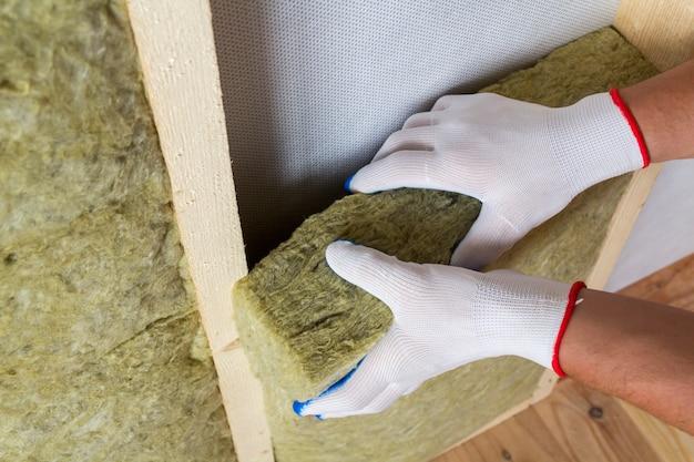 コールドバリアの将来の壁のための木製フレームのロックウール断熱材スタッフを絶縁する白い手袋で労働者の手のクローズアップ。快適な暖かい家、経済、建設、改修のコンセプト。