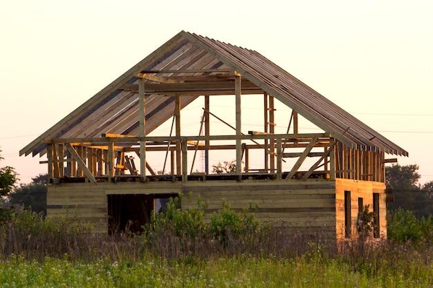 緑のフィールドで建設中の自然生態木材の新しいコテージ。木製の壁と急な屋根フレーム。プロパティ、投資、専門的な建物と再建のコンセプト。