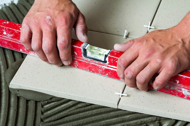 セラミックタイルと瓦職人のためのツール。労働者の手が床タイルを取り付けます。改築、改修-セラミックタイルの床の接着剤、モルタル、レベル。