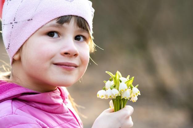 早春のスノードロップの花の束を屋外に保持している幸せな子供の女の子の肖像画。