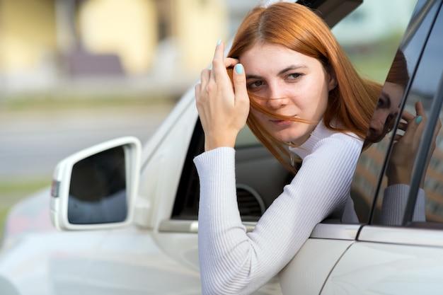 Водитель молодой женщины смотря из окна автомобиля.