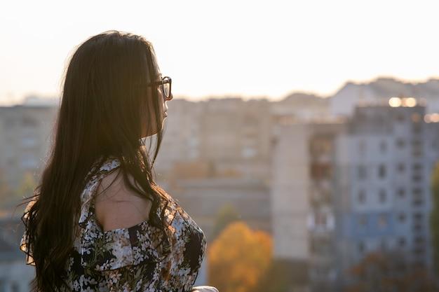 暖かい夏の日の屋外の都市景観を探しているメガネで幸せな黒い髪の女性の背面図。