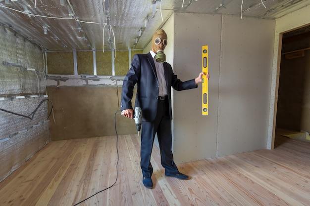 修理中の部屋の中のビジネスマンスーツとガス防護マスクの奇妙な男は、電動ドライバーとレベルツールを保持しています。