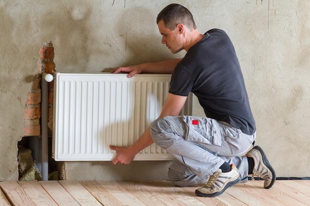 Молодой красивый профессиональный работник водопроводчика устанавливая радиатор отопления в пустую комнату заново построенной квартиры или дома. концепция строительства, обслуживания и ремонта.