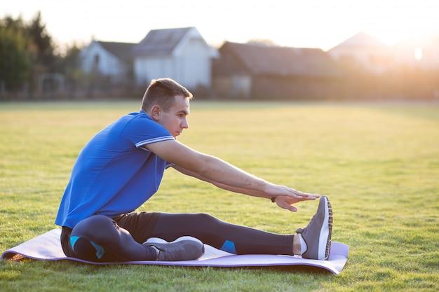 朝の野外で実行する前にストレッチ体操を行う陽気な若者。