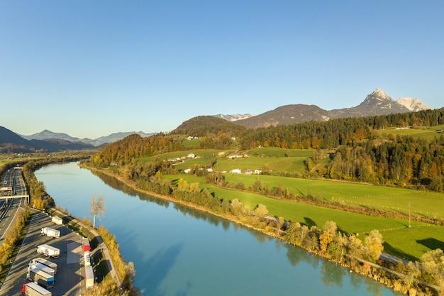 Аэрофотоснимок автомагистрали между штатами с быстрым движением возле большой реки в горах альп
