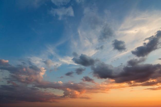 日の出または日没の空のパノラマ。澄んだ空に明るいオレンジ黄色の太陽に照らされた暗い青色の雲の美しい景色。自然の美と力、気象学、気候変動の概念。