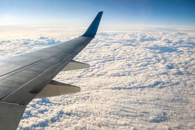 晴れた朝に曇りの風景の上を飛んでいる航空機の白い翼の飛行機からの眺め。空の旅と輸送の概念。