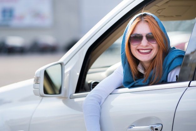 Молодой модный улыбается женщина водитель, глядя в окно за рулем автомобиля.