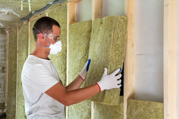 防寒ゴーグルと防寒マスクの作業員は、防寒壁の将来の家の壁のために木枠のロックウール断熱材を断熱します。快適な暖かい家、経済、建設、改修のコンセプト