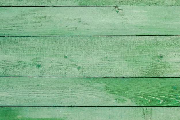 自然風化した木製の板の背景。緑のボードパネルに古い塗装