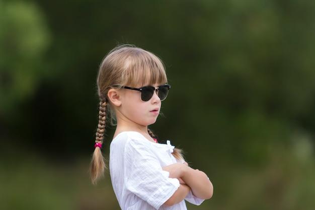 Портрет милой довольно забавной маленькой девочки со светлыми оплетками в белом платье и темных солнцезащитных очках.