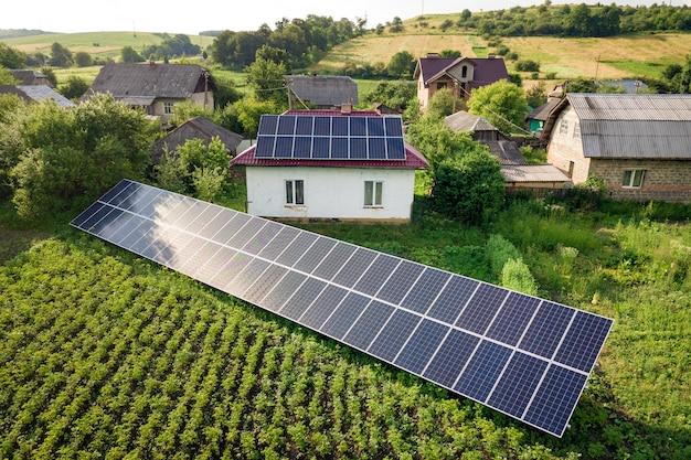 クリーンエネルギーのための青い太陽電池パネルが付いている家の空撮。