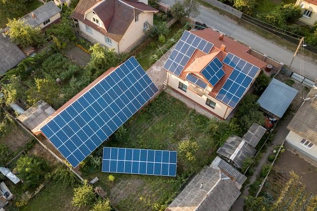 屋根の上の青い光沢のある太陽光写真太陽光発電パネルシステムと新しいモダンな住宅コテージの空中のトップビュー