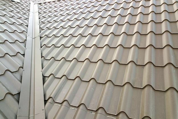 金属タイルシートで覆われた新しい家の屋根構造のクローズアップ。