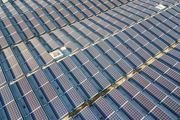 産業用建物の屋根に取り付けられた多くの太陽光発電太陽電池パネルの空撮。