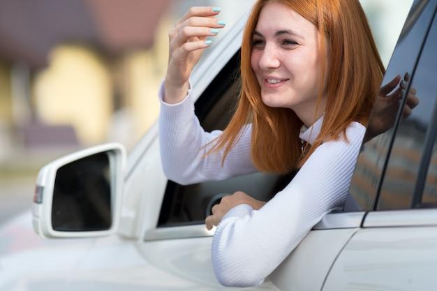 Молодая женщина с рыжими волосами за рулем автомобиля.